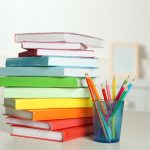 Colorful books and pencil on table in room