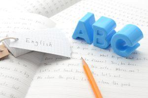 英語教育イメージ―ノートの上のアルファベットのおもちゃ