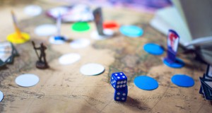 Dice are on the background blurred colorful fantasy Board games in the world map. moments in gaming dynamics